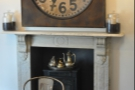 The room is dominated by the fireplace, with its cast-iron stove and awesome clock!