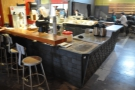 Looking back at the counter, with seating on the left and on the opposite side.