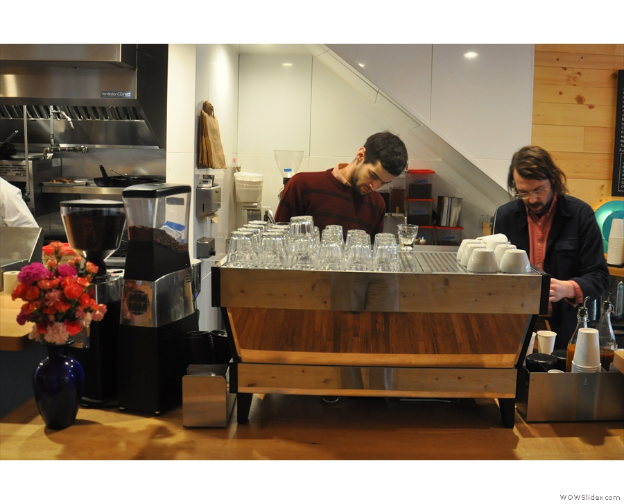 Baristas at work. There's a three-group La Marzocco with a pair of grinders...