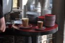 Various cups of coffee, waiting to be taken to the customers. Frankly either of those would have done for me.