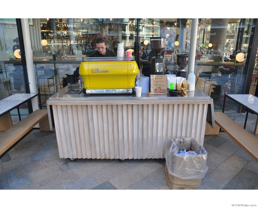 To the left of the door, there's this mobile counter with its bright yellow La Marzocco.