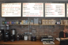The coffee menus are on diner-style menus hanging on the wall behind the counter.