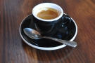 My espresso on its own, in a classic, black cup.