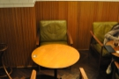 There are small, round tables with comfortable chairs up against the right-hand walll...