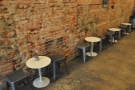The seating is a row of two-person round tables against the bare-brick wall on the left.