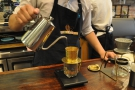 A steady, continuous pour, distributing the water evenly across the surface of the coffee.