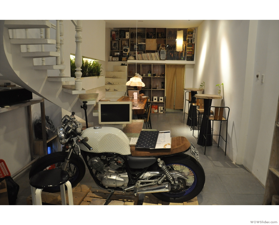 Beyond the counter is a motorcycle and a flight of stairs...