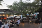Beyond this, there is more seating in front of the coffee shop, clustered around a tree.