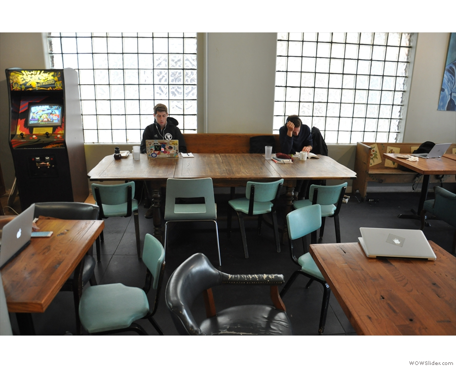 ... incluidng a communal table with a long wooden bench seat against the right-hand wall.