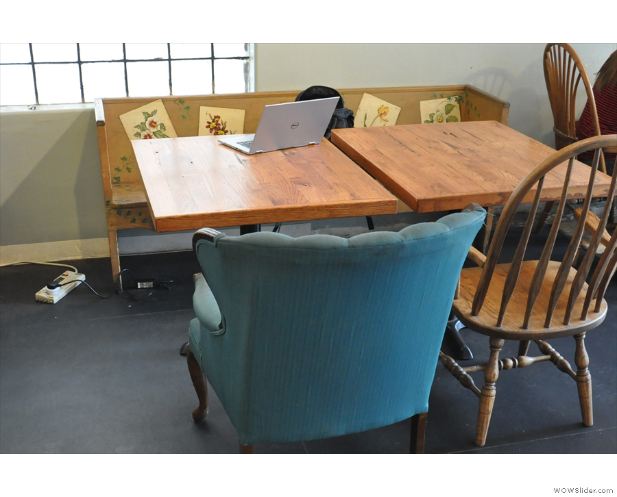 There's a smalerl wooden bench seat next to it with two smaller tables.