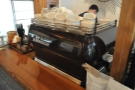 The espresso machine is at the far end, beyond the two grinders.