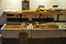 The cakes are on the top shelf, while sandwiches are in the basins below.