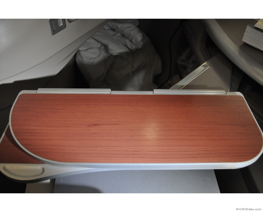 The table hinges out, like in the 787, from the console at the side...