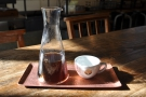 My coffee in the sun, served in the beaker, with a cup on the side, all on a little tray.
