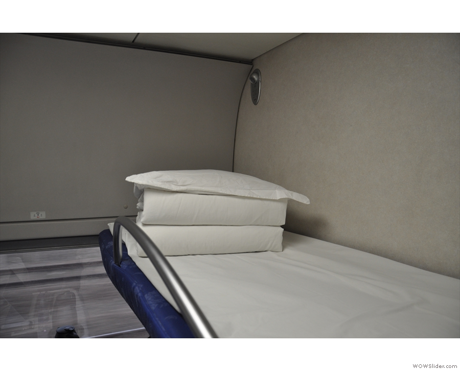 Bedding is a pillow, a sheet and a duvet. A bar on the side of the upper bunk doubles...