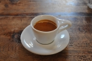 ... and the resulting espresso, served in a classic white cup with oversized handle.