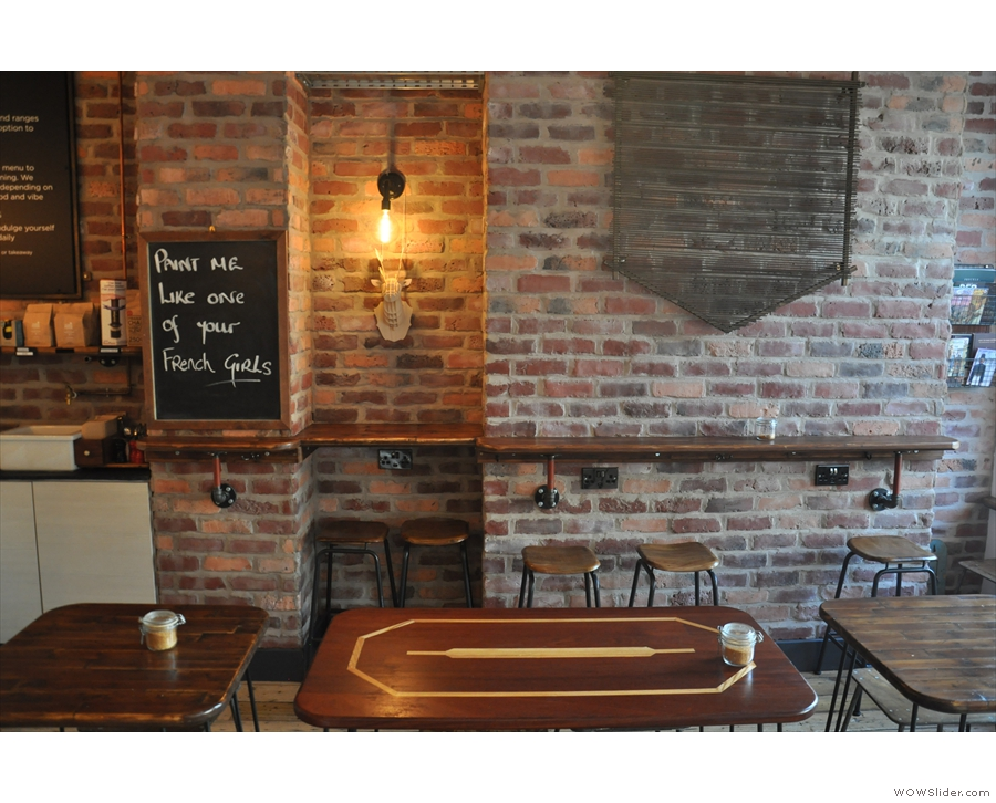 Another bar runs along the exposed brick of the right-hand wall.