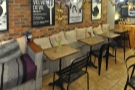 Next comes a row of four two-person tables lining a bench along the brick wall.