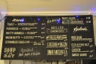 The menus are displayed on blackboards above the counter, with food on the left...