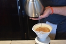 Jacob fills up the V60, pouring continuously, moving the spout of the kettle...