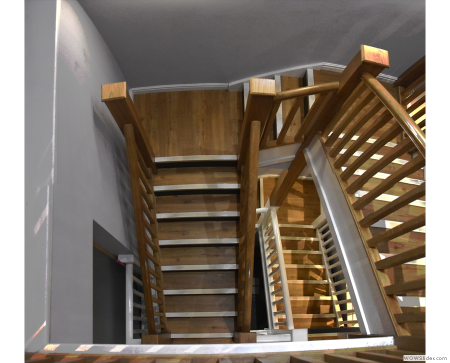 ... a central, wooden stairwell which heads down, doubling back on itself.