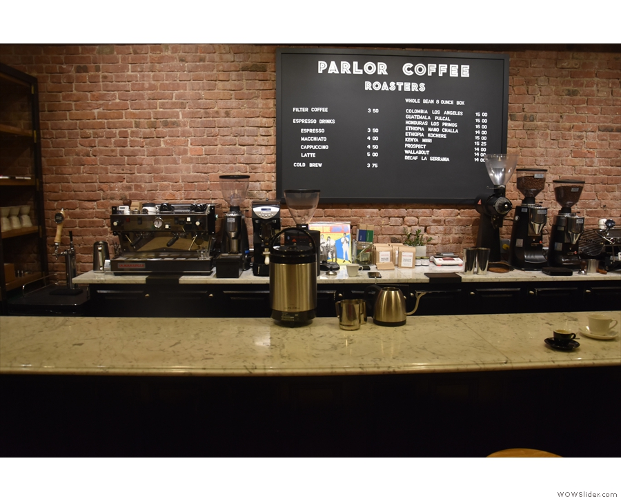 The counter has a central menu on the back wall, flanked by two espresso machines.