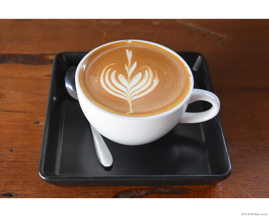 My flat white, made with the house blend, and served on a little tray.