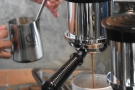While the espresso extracts, the barista foams the milk.