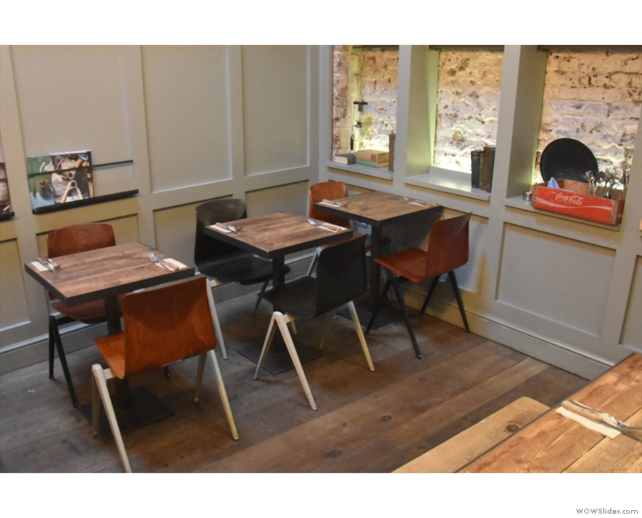 ... with four more two-person tables, this time with chairs, against the back wall.