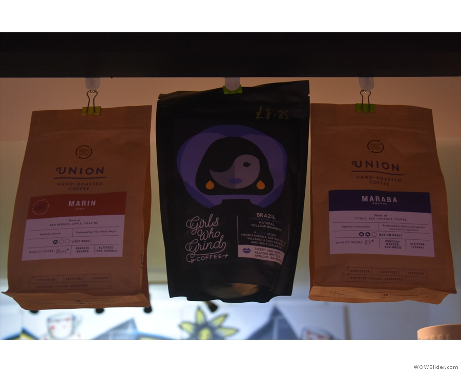 The coffee choices hang, in the form of bags of coffee, from a line above the counter.