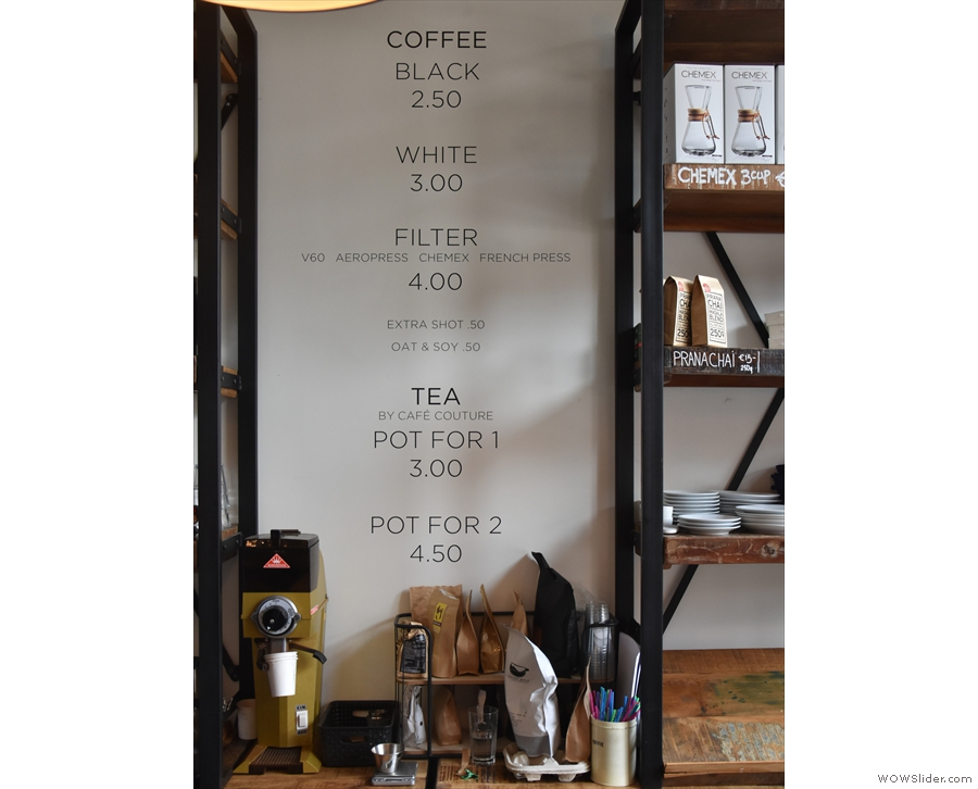 The simplified drinks menu is on the wall behind the till...