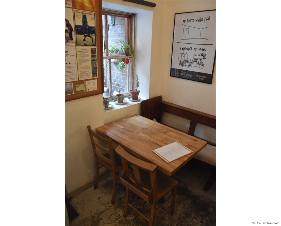 There are a pair of four-person tables to the left of the door: this one by the window...