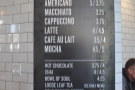 The coffee menu is on a pillar to the right of the till...