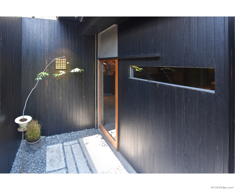 A narrow, sheltered path leads down the side of the building, to a sliding glass door...