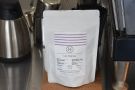 The choice of single origin for the batch-brew is displayed on the counter by the till...