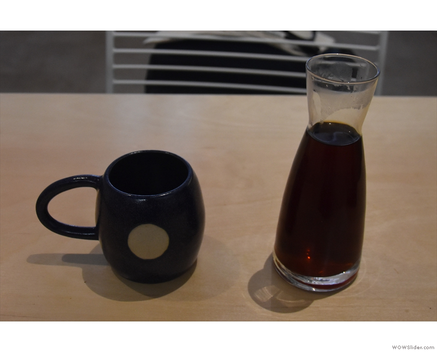 The coffee is served in a tall, narrow-necked carafe with a cup on the side.
