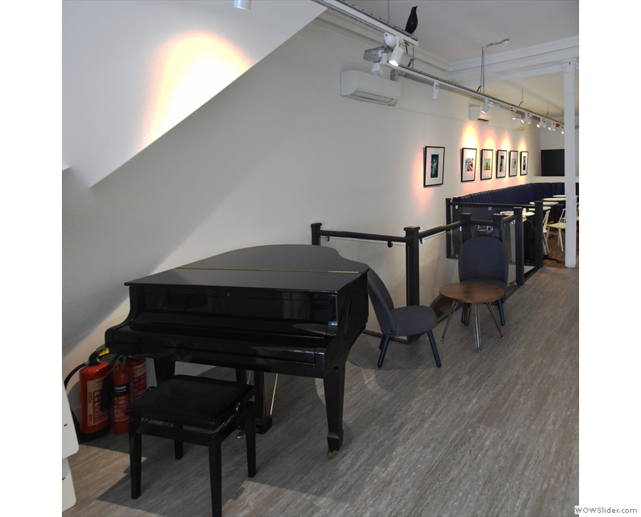 ... where there's a baby grand piano, nestling under the external staircase.