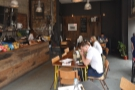 There are two tables in the middle, a square one, and a longer, communal table...