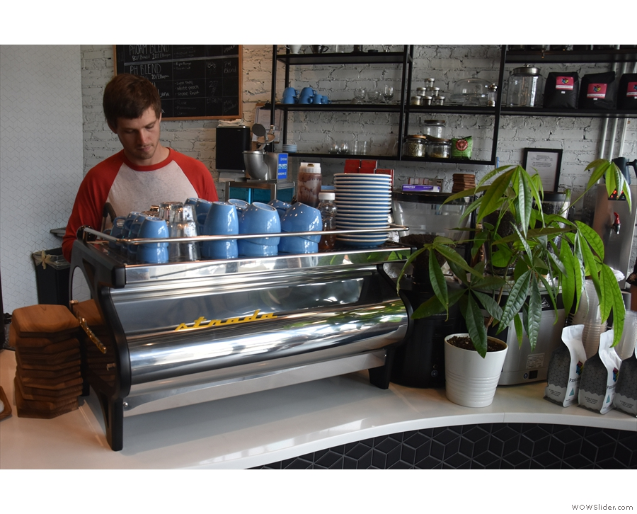 After the till, on the curved part of the counter, is the two-group La Marzocco Strada...