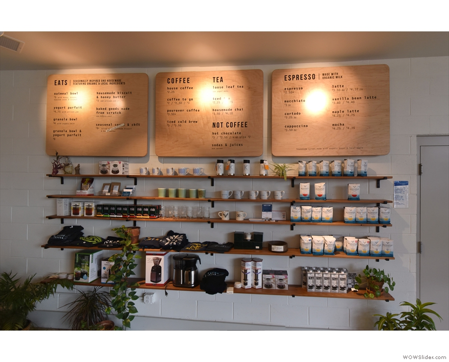 The retail shelves are on the angled section of the back wall, with the menus above.