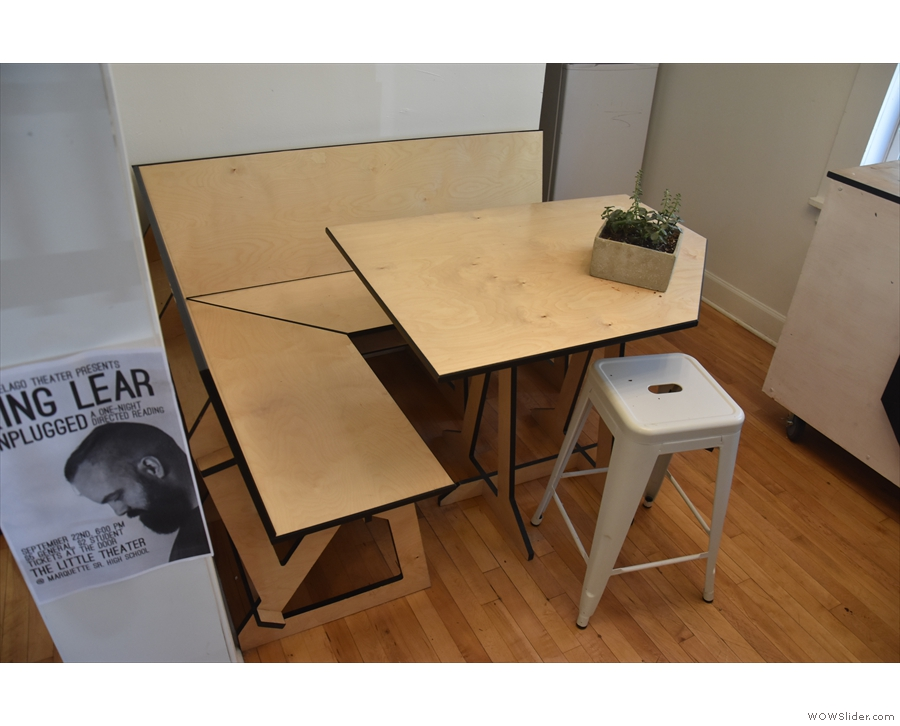 There's an L-shaped bench, with a rectangular table that's missing a corner.