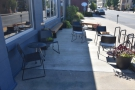 There's a raised outdoor seating area to the right, with three tables and two benches.