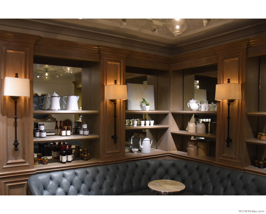 The elegant, wood-panelled, mirror-backed shelves along the front & left-hand walls...