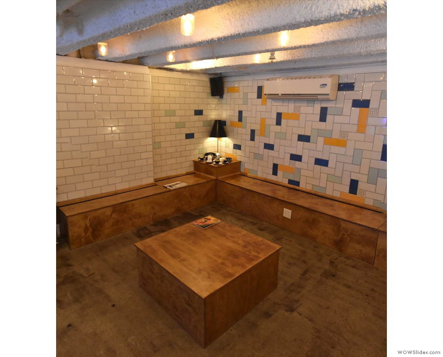 Wooden box-benches run around the three walls, with a low coffee table in the centre.