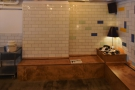 The left-hand wall, opposite the stairs, has plain tiling above...