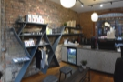 There's a set of retail shelves on the exposed bricks of the left-hand wall...