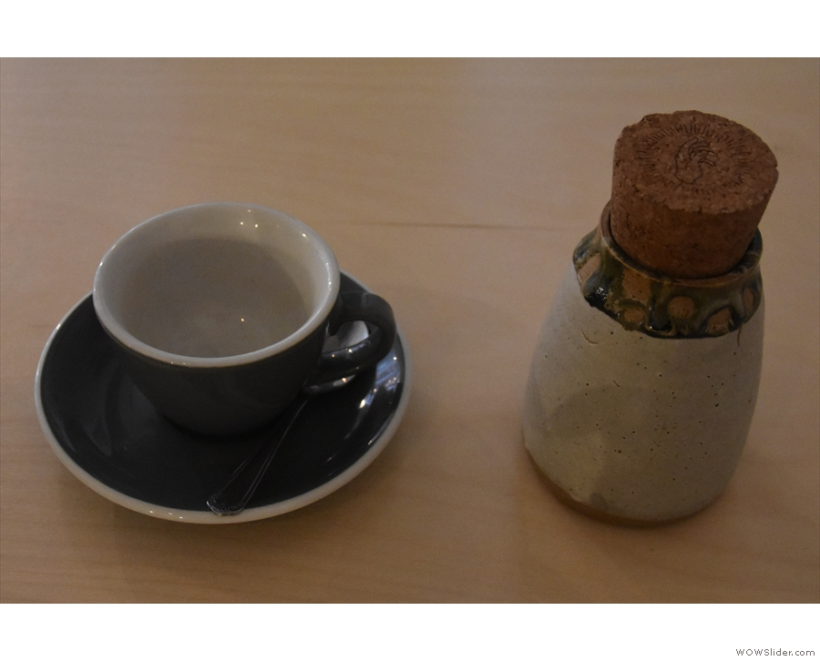 The presentation is excellent, with the coffee in a ceramic flask, cup on one side.