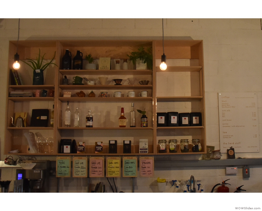 Coffee and coffee-kit on the wall behind the counter.