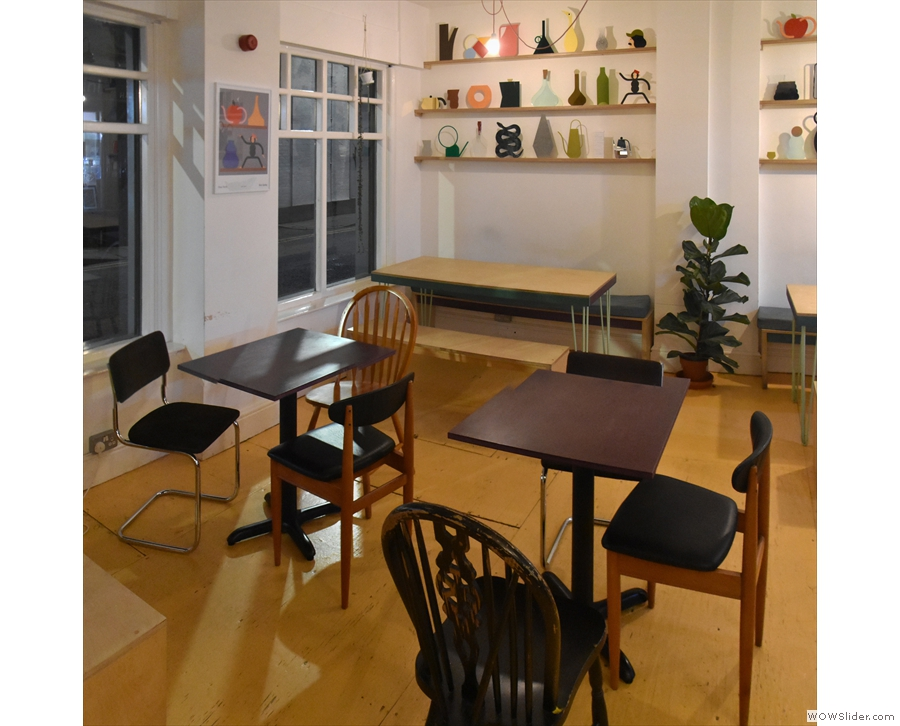 ... are two square tables, followed by more communal tables against the left-hand wall.