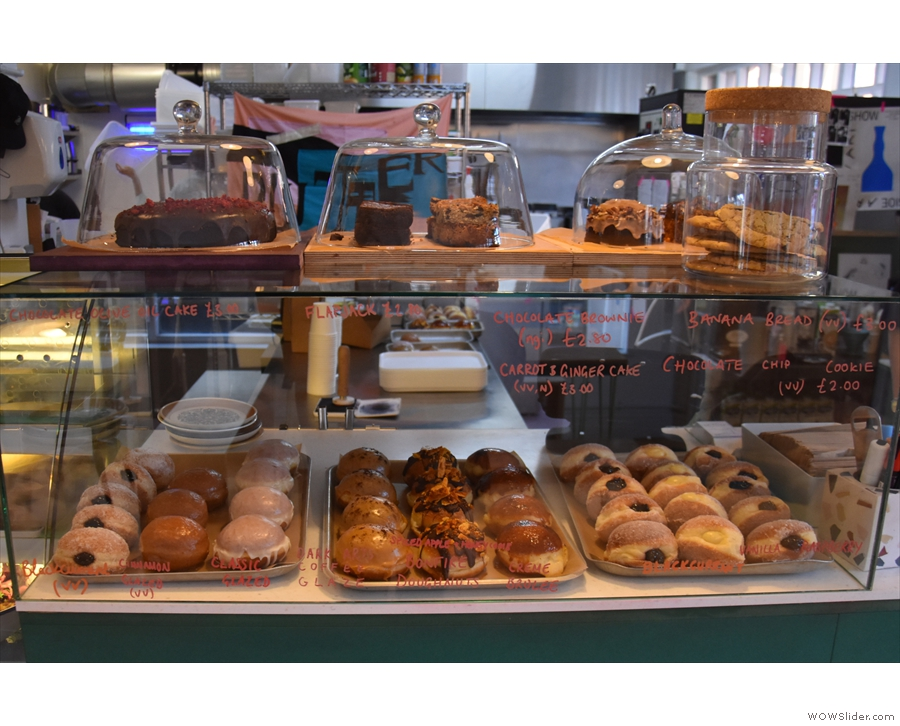There is a large display case to the left of the till which contains the cakes on top...